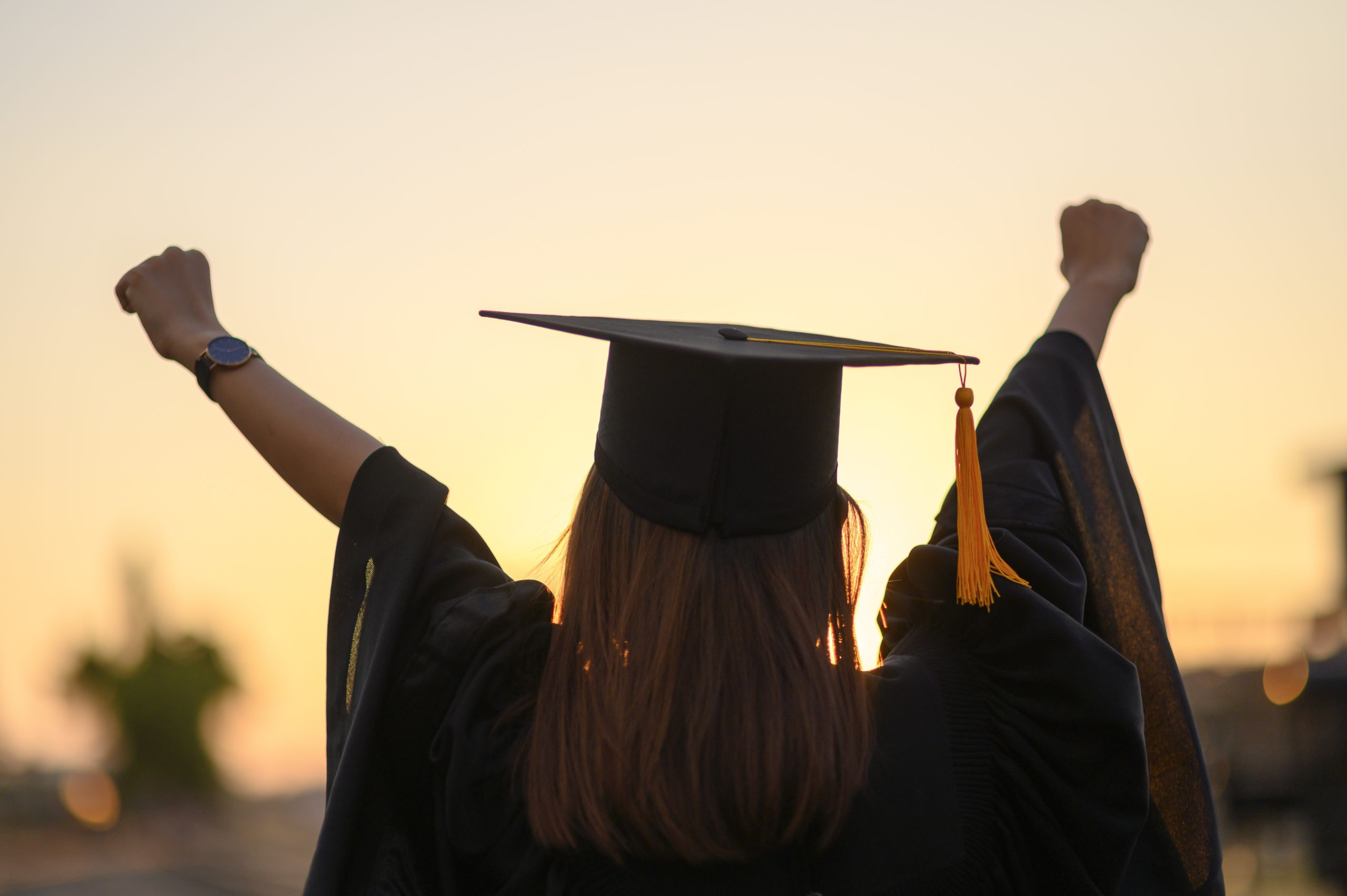 Female graduate with hands in the air